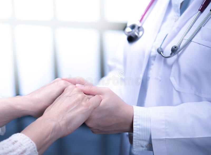 Medical doctor reassuring patient by holding patient's hands in hospital setting royalty free stock photo
