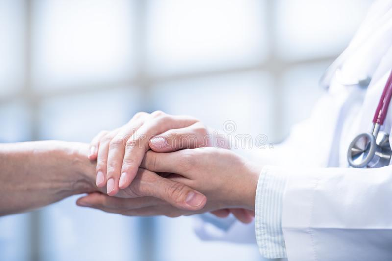 Medical doctor reassuring  patient by holding patient's hands in hospital setting stock photography