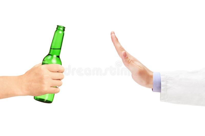Medical doctor refusing a bottle of beer stock image