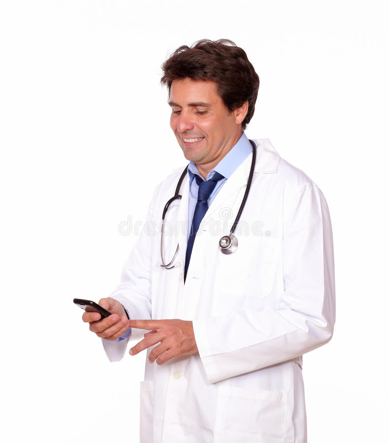 Medical doctor sending message by cellphone. Portrait of a medical doctor sending message by cellphone over white background stock image