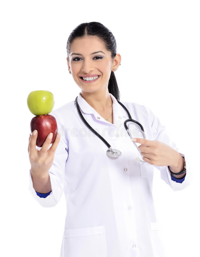 Medical doctor showing apple. Doctor woman giving / showing apple. Young female medical professional isolated on white background. focus an apple royalty free stock photography