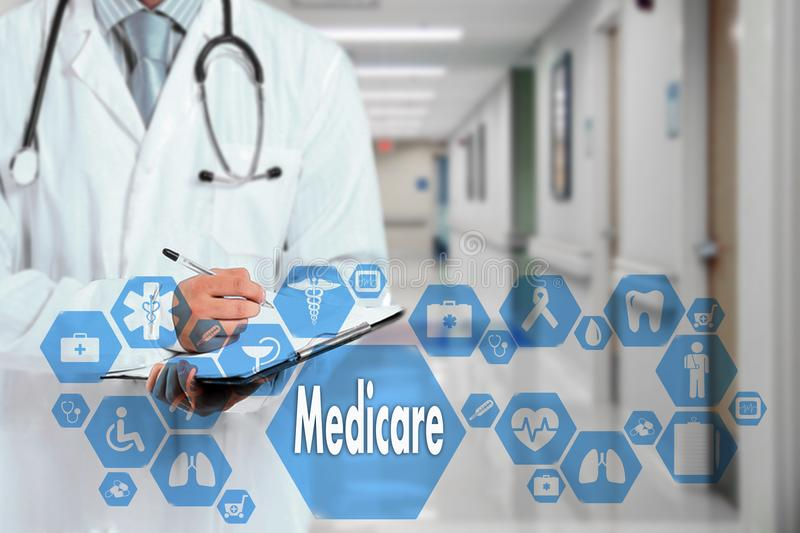 Medical Doctor with stethoscope and Medicare icon in Medical net. Work connection on the virtual screen on hospital background.Technology and medicine concept stock image