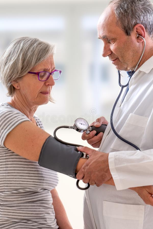 A medical doctor takes a patient s blood pressure. stock images
