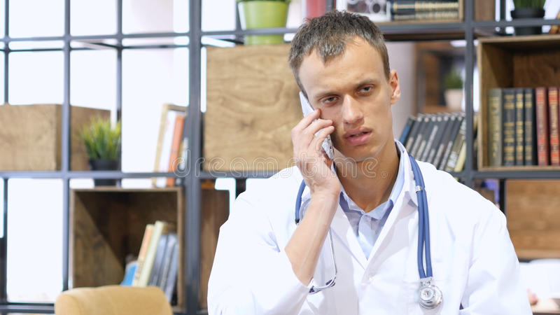 Medical doctor talking on phone at office royalty free stock photo