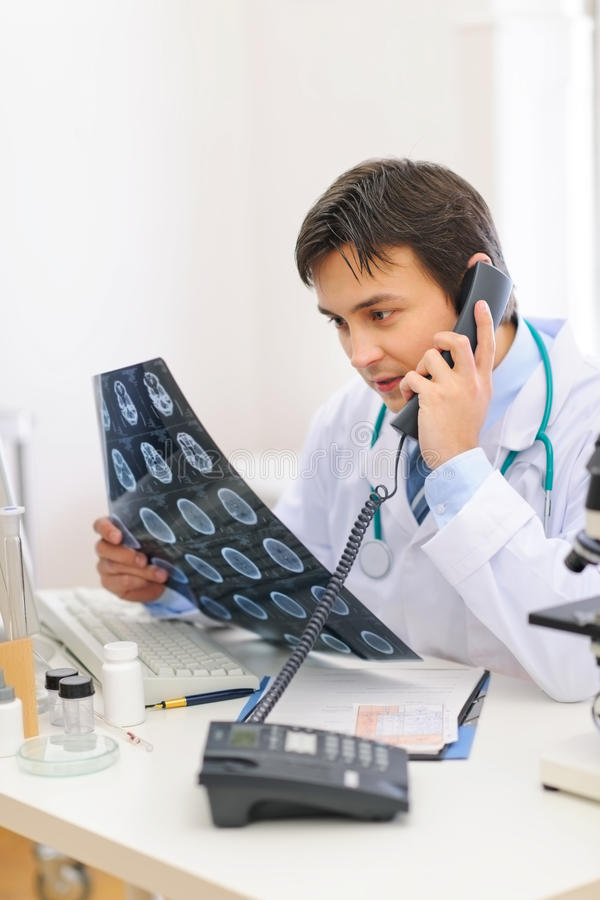 Medical doctor with tomography speaking phone stock photos