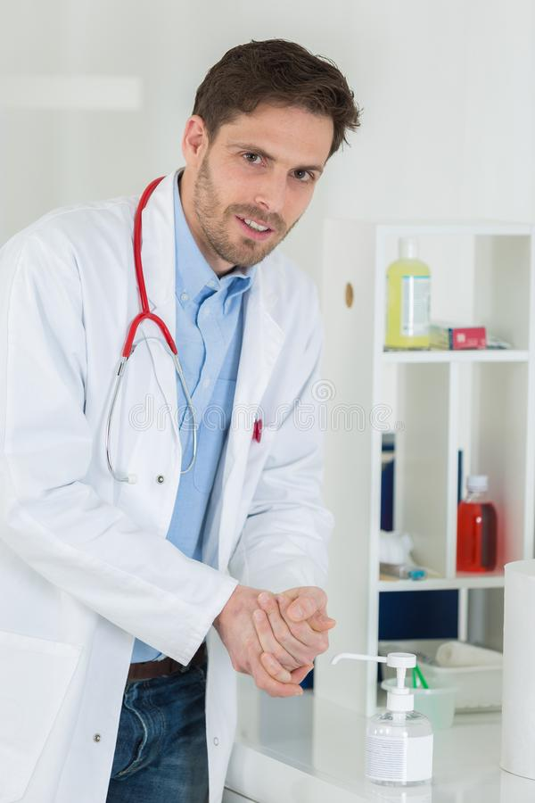 Medical doctor using sanitizer dispenser in clinic royalty free stock photos