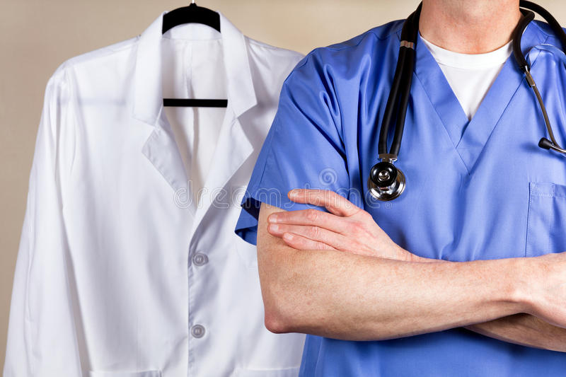 Medical doctor wearing blue scrubs with white consultation coat. Close up partial view of medical doctor wearing scrubs and stethoscope with medical coat in stock images