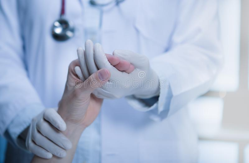 Medical  doctor wearing latex gloves holding patient's hand to give support in hospital setting stock photo