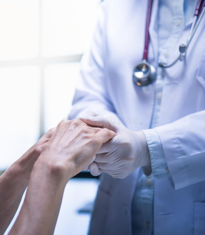 Medical  doctor wearing latex gloves holding patient's hand to give support in hospital setting stock images