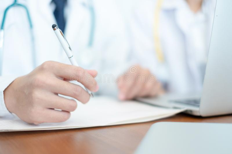 Medical doctor in white uniform writing result and prescription royalty free stock photography
