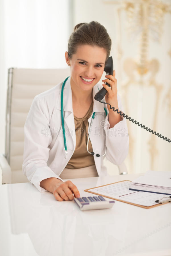 Medical doctor woman with calculator talking phone. Happy medical doctor woman with calculator talking phone royalty free stock photo