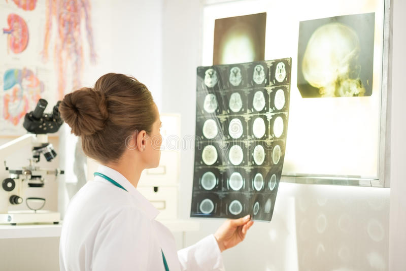 Medical doctor woman looking on tomography. In office royalty free stock photography