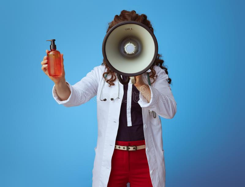 Medical doctor woman with megaphone showing sun cream on blue. Elegant medical doctor woman in bue shirt, red pants and white medical robe with megaphone showing stock photos