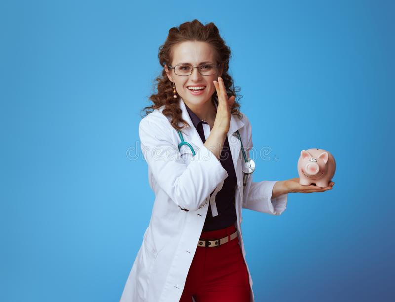 Medical doctor woman with piggy bank telling exciting news. Happy elegant medical doctor woman in bue shirt, red pants and white medical robe with piggy bank stock image