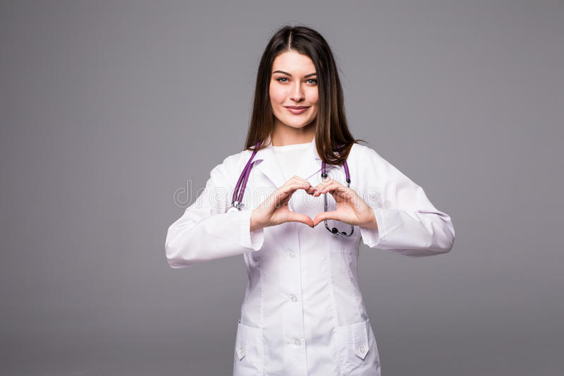 Medical doctor woman showing heart shape gesture on grey. Closeup on medical doctor woman showing heart shape gesture royalty free stock image