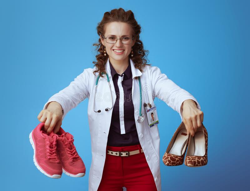 Medical doctor woman showing sneakers and high heel shoes. Smiling modern medical practitioner woman in bue shirt, red pants and white medical robe showing royalty free stock images