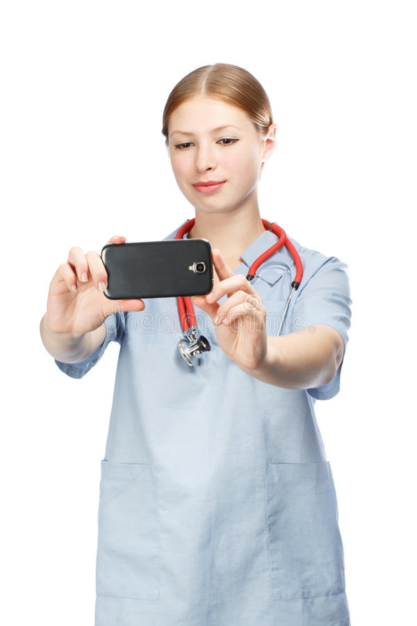 Medical doctor woman with stethoscope taking photos with smartphone. Isolated on white background royalty free stock image