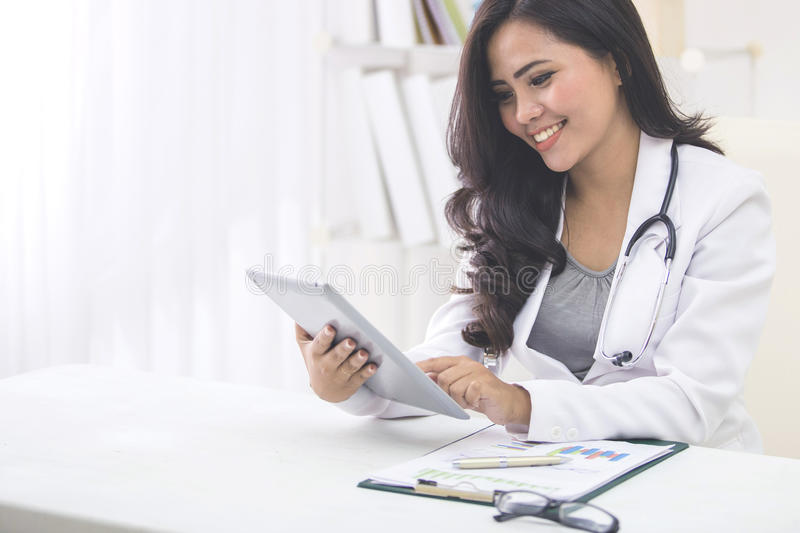 Medical doctor woman with stethoscope using tablet pc. Smiling medical doctor use stethoscope and read her tablet pc in her office royalty free stock images