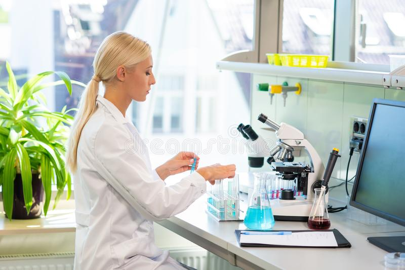 Medical doctor working in research lab. Science assistant making experiments. Laboratory tools: microscope, test tubes. Medical doctor working in research lab stock photo