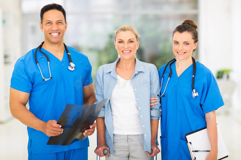 Medical doctors patient. Portrait of happy medical doctors with middle aged patient royalty free stock images