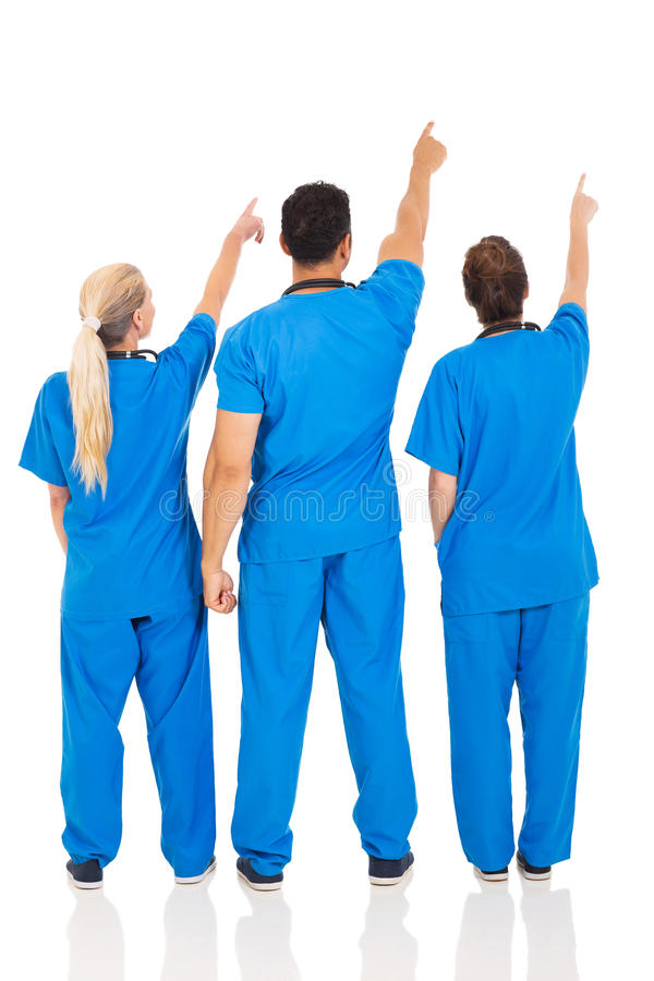 Medical doctors pointing. Rear view of medical doctors pointing empty space stock photos