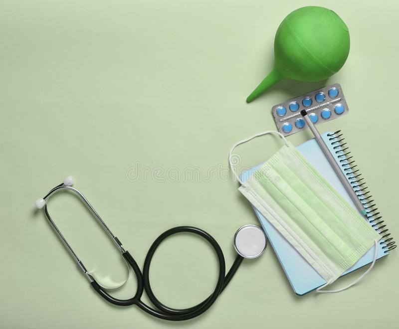 Medical equipment on a blue background. Enema, blisters pills, n. Otepad, stethoscope, syringe, thermometer. Medical concept, top view, flat lay style stock photos