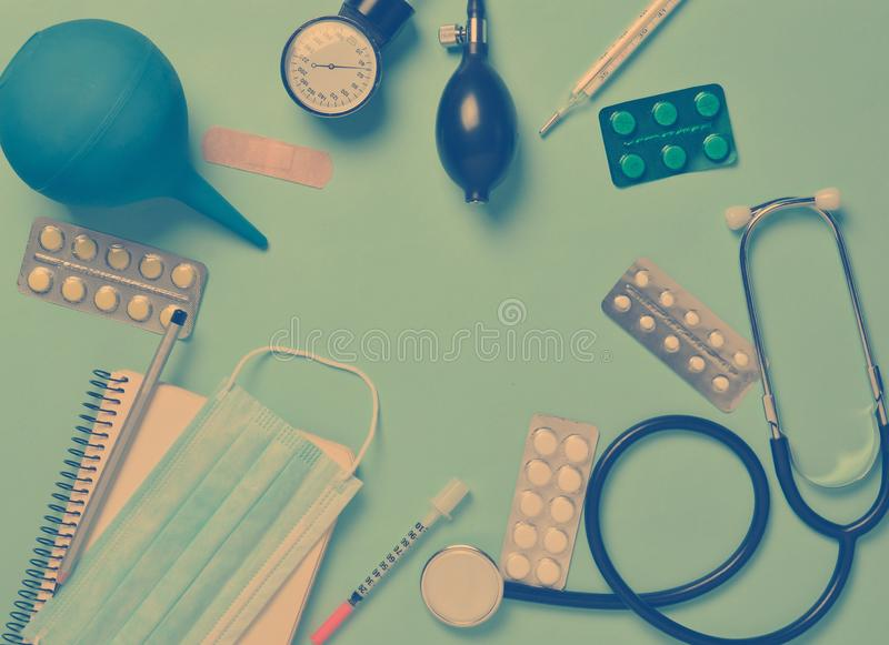 Medical equipment on a blue background. Enema, blisters pills, n. Otepad, stethoscope, syringe, thermometer, manometer. Medical concept, top view, flat lay style stock photo