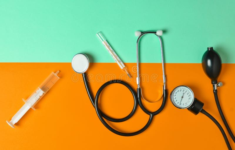 Medical equipment on a colored paper background. Stethoscope, syringe, thermometer, tonometer. Top view, flat lay stock image