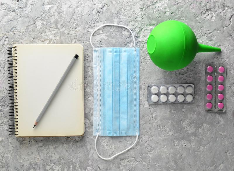 Medical equipment on a gray concrete background. Enema, pills, n. Otepad. Medical concept, top view, flat lay style royalty free stock image