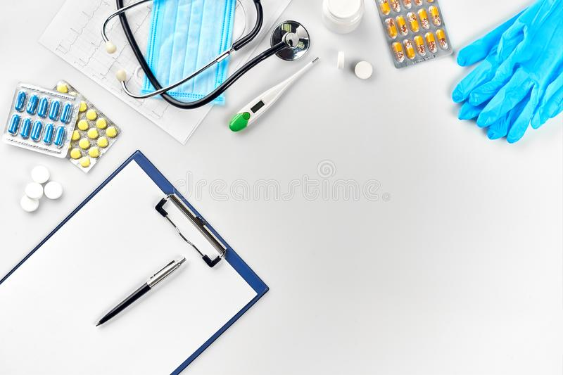 Medical equipment : pills, mask, blue gloves, thermometer and stethoscope, white blank with a pen on white background stock photo