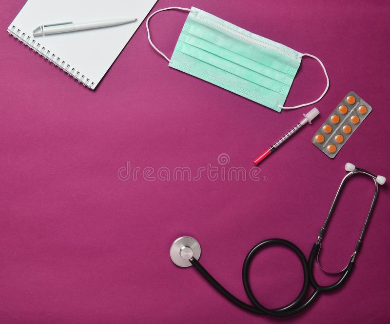Medical equipment on a red background. Blisters pills, noteook,. Stethoscope. Medical concept, top view, flat lay style stock images