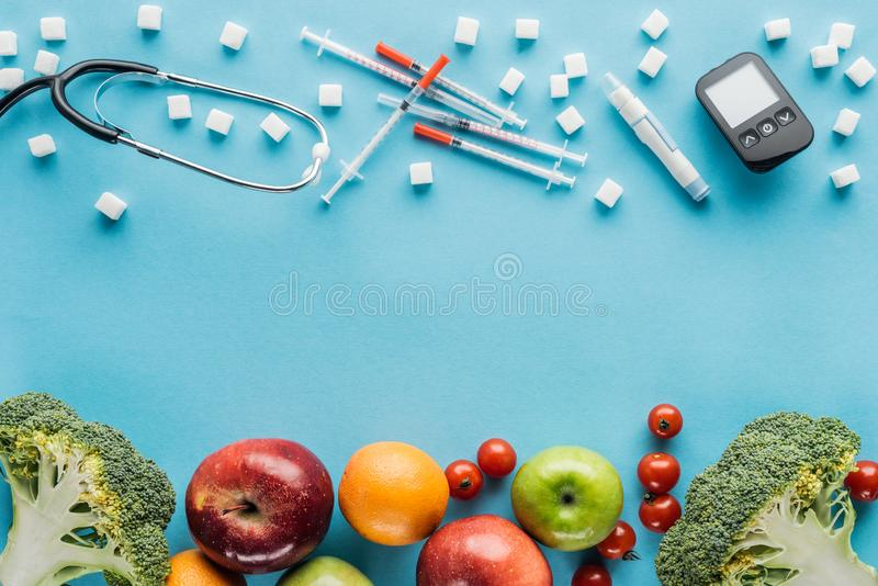 Medical equipment, sugar cubes and fruits with copy space. On blue background stock photos