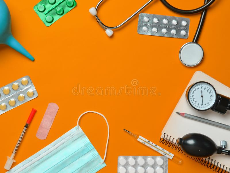 Medical equipment on a yellow background. Enema, blisters pills, notepad, stethoscope, syringe, thermometer, manometer. Medical c. Oncept, top view, flat lay stock photos