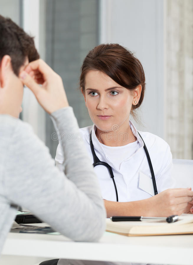 Medical exam. Patient explaining problem to doctor royalty free stock images