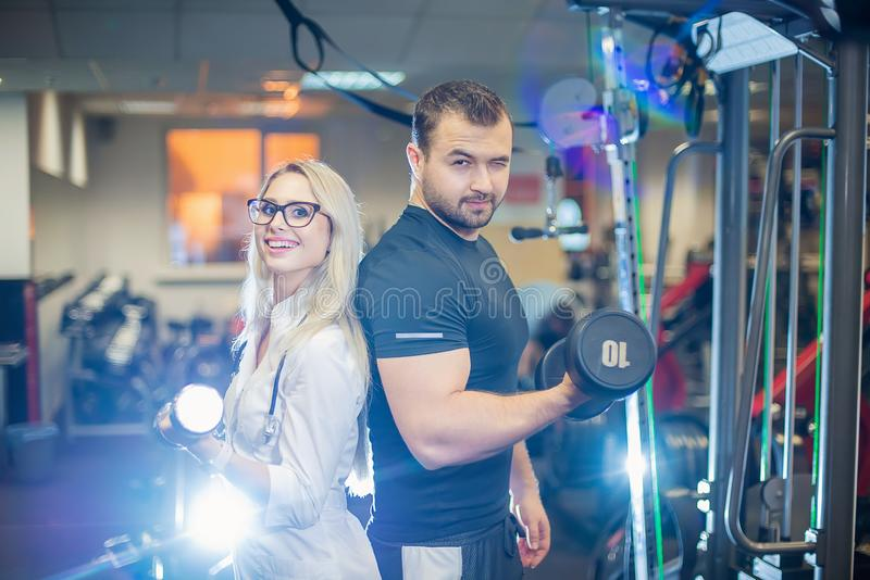 Medical examination. Attractive doctor and athlete posing with dumbbells. Beautiful woman doctor and patient man talking royalty free stock photo