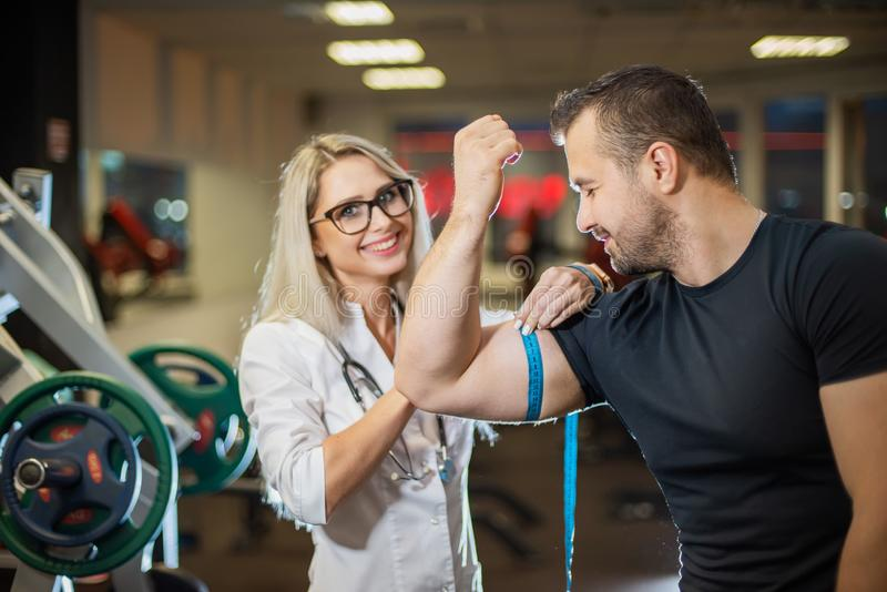 Medical examination. An attractive doctor measures the volume of an athletes biceps. Female doctor monitors muscle gain royalty free stock image