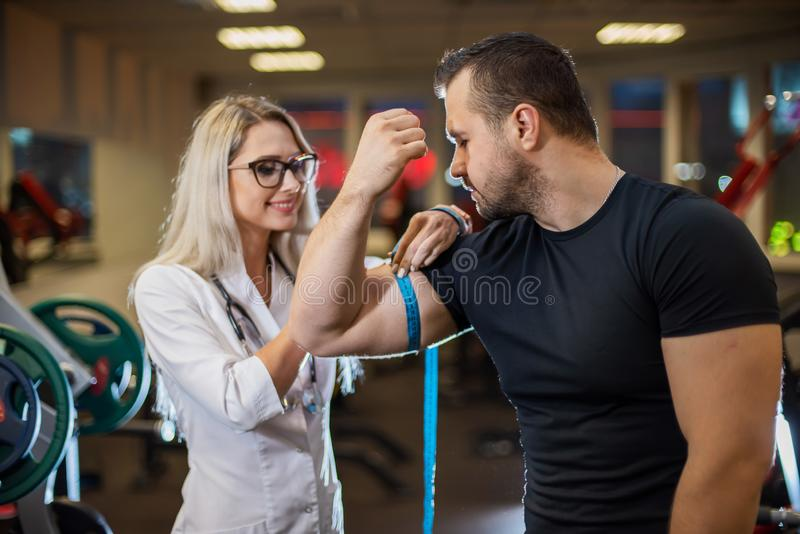 Medical examination. An attractive doctor measures the volume of an athletes biceps. Female doctor monitors muscle gain stock photography