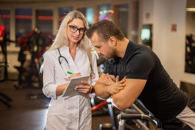 Medical examination. heart rate The doctor measures the pulse during a stress test. A female doctor measures a male stock photography
