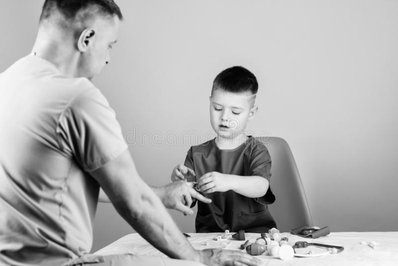 Medical examination. Hospital worker. Medical service. Analysis laboratory. Kid little doctor sit table medical tools. Health care. Pediatrician concept. Boy stock image