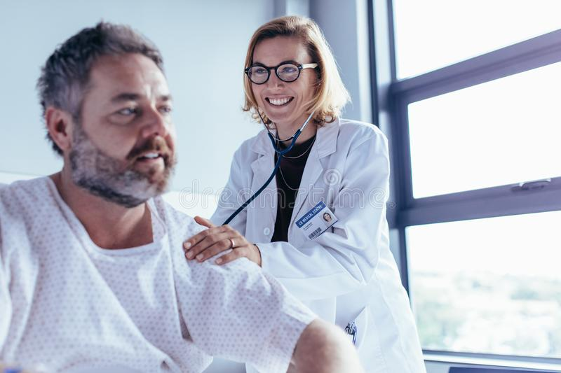 Medical examination of mature man in hospital ward. Medical examination of mature male patient in hospital ward. Woman doctor checking heartbeat of hospitalised stock image