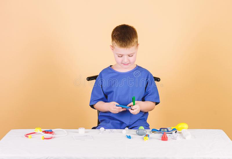 Medical examination. Medical education. Play game. Boy cute child future doctor career. Healthy life. Kid little doctor. Sit table with stethoscope and medical stock images