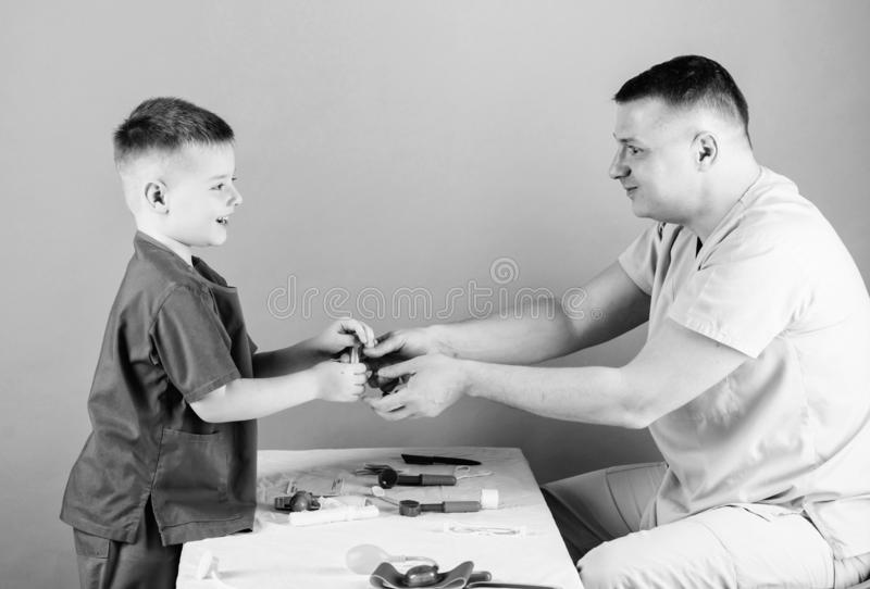 Medical examination. Medical service. Man doctor sit table medical tools examining little boy patient. Health care. Pediatrician concept. Child care. Careful royalty free stock photography