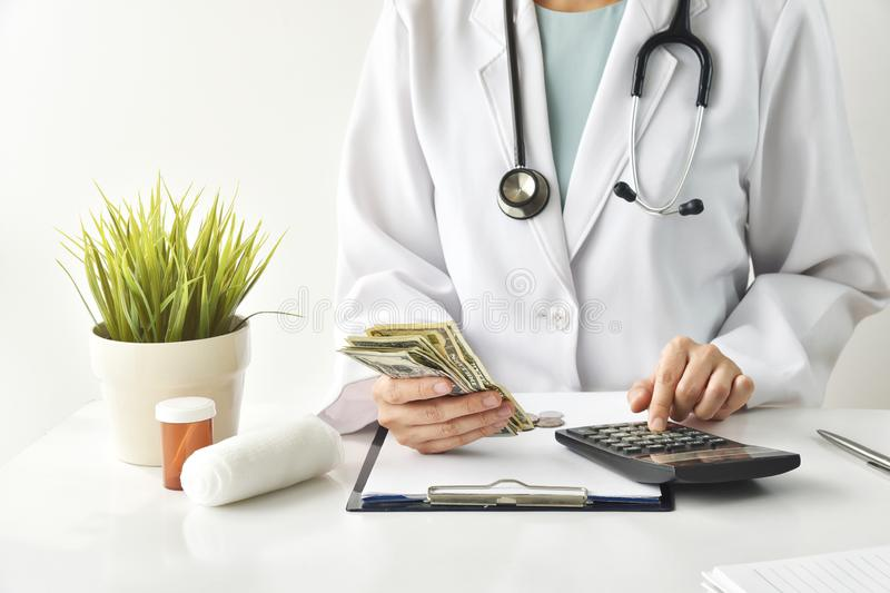 Medical fee, Health insurance, Doctor holding dollar banknotes and calculate the examination charges. stock image