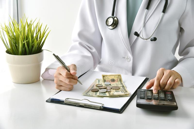 Medical fee, Health insurance, Doctor writing medication note and calculate the examination charges in hospital. stock images