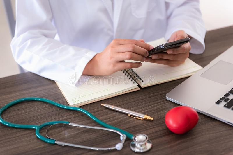 Medical female doctor is using cellphone while waiting for her patient in examination room. Work office royalty free stock images