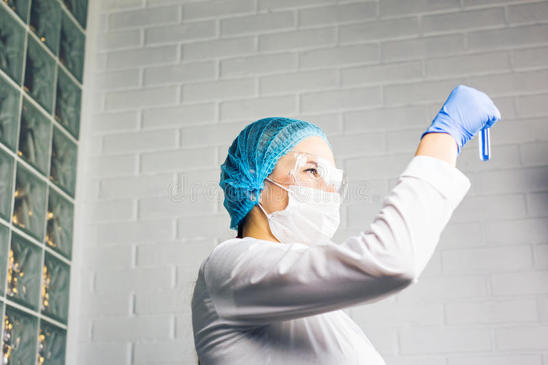 Medical female researcher holding test tube with blue liquid. Medical researcher holding test tube with blue fluorescent liquid stock images