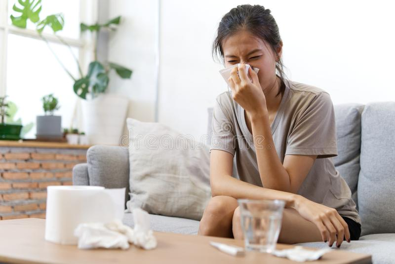Sick Asian young woman sneeze at home on the sofa with a cold, she is  blowing her nose. royalty free stock photography