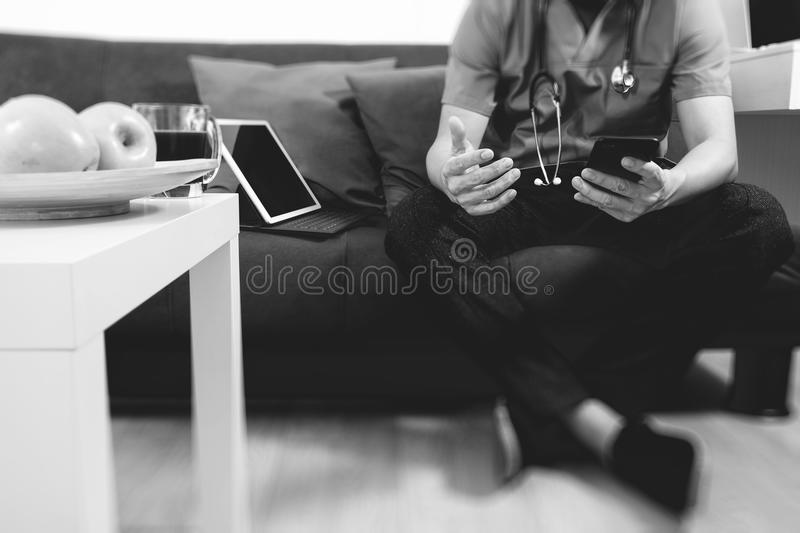 Medical and Health context,doctor hand working with smart phone,digital tablet computer,stethoscope,sitting on sofa in living stock photos