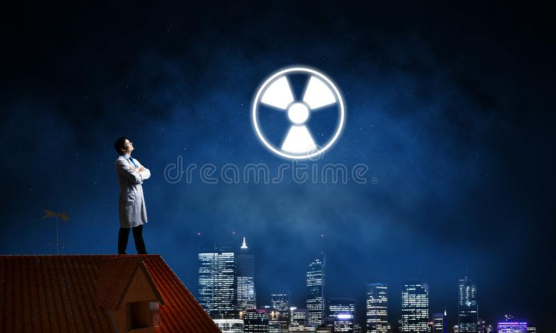 Medical industry and radioactive materials. Young medical industry employee standing on brick house roof and interracting with glowing radioactive symbol with stock photography
