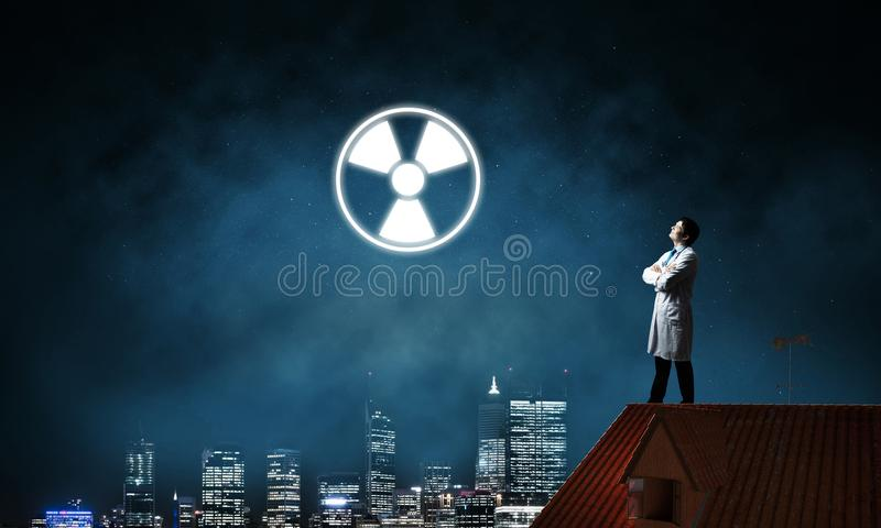 Medical industry and radioactive materials. Young medical industry employee standing on brick house roof and interracting with glowing radioactive symbol with royalty free stock image